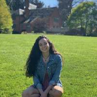 Juliana, smiling, sitting on the grass in front of the Manor House on a sunny day. Student-suppli...