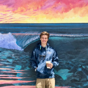 Max, holding a cup of coffee, standing in front of a wall with a painted mural of the ocean.