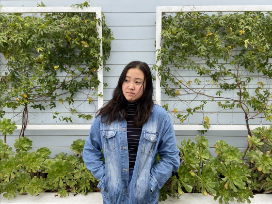 Alys, looking upward, standing in front of a vine-covered wall.