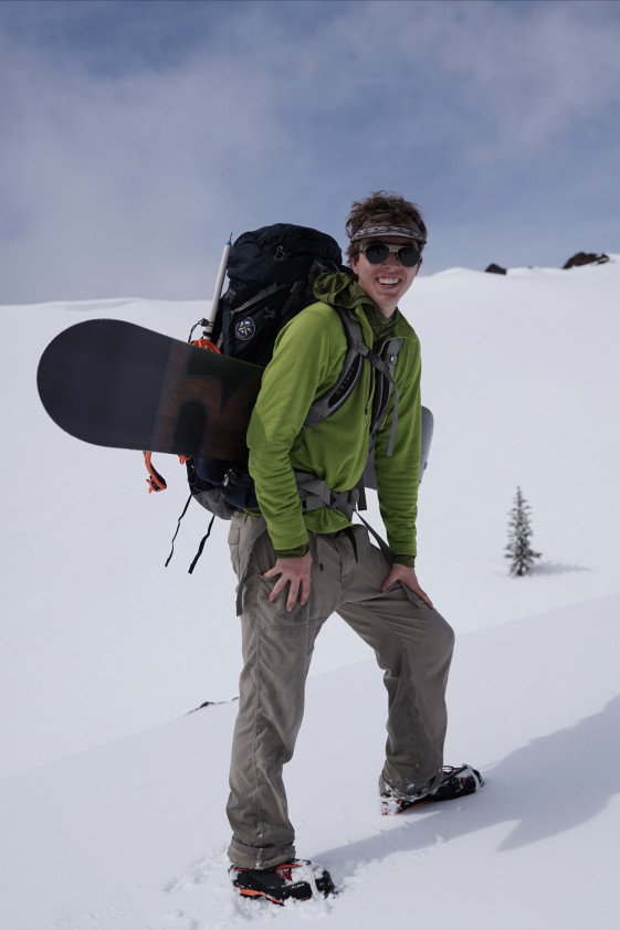 Max, in green jacket and climbing gear, smiling on a snow-covered mountain peak.