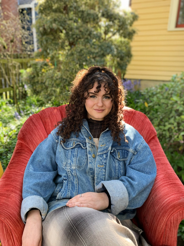 Shoshana, smiling, while reclining in a red chair in front of trees.