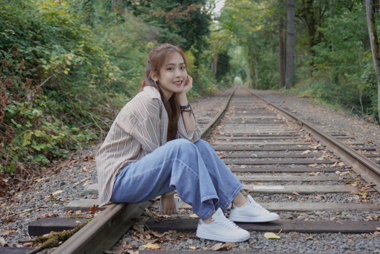 Evangeline, sitting on railroad tracks, smiling into the camera.