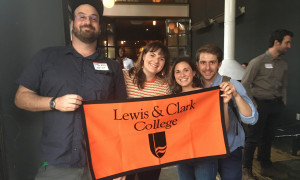 Lewis & Clark alums holding the college banner.